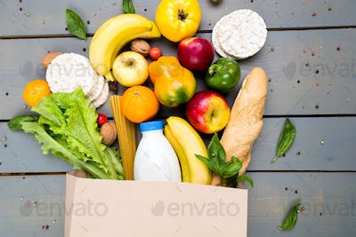 Grocery shopping concept. Different food in paper bag on wooden background.  Flat lay.