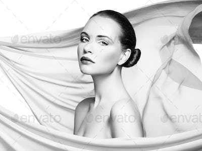 Portrait of young beautiful woman against flying fabric. Beauty