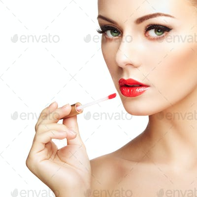 Beautiful young woman paints lips with lipstick. Perfect make-up