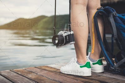 Young traveler standing and looking at the nature with camera and backpack