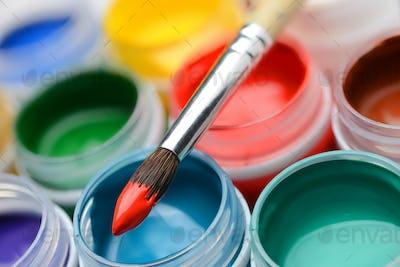 Gouache paint jars and paintbrush
