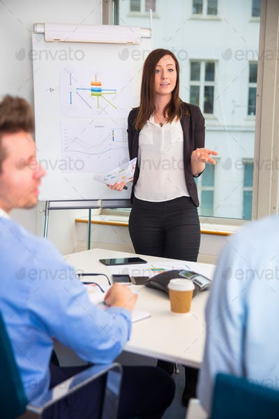 Female Professional Giving Presentation To Colleagues