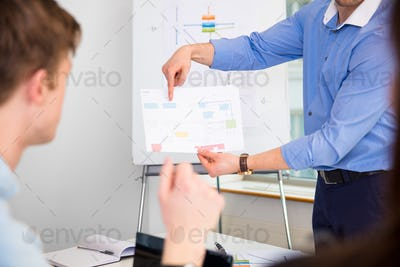 Professional Showing Chart To Coworker In Office