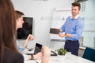 Businessman Showing Digital Tablet To Colleagues