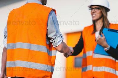 Business handshake on construction site