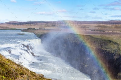 rainbow over Gullfoss waterfall in canyon