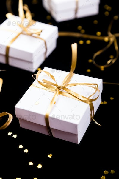 White gift boxes with gold ribbon on shine background. Close up.