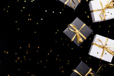 Black and white gift boxes with gold ribbon on shine background. Flat lay. Copy space.