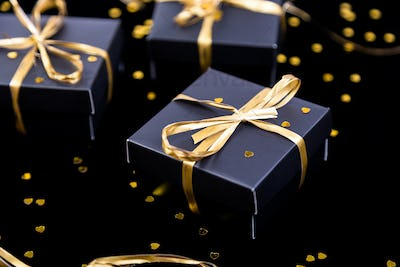Black gift boxes with gold ribbon on shine background. Close up.