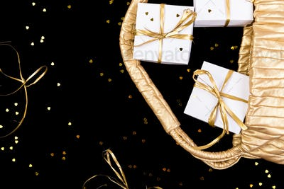 White gift boxes with gold ribbon pop out from golden bag on shine background. Flat lay