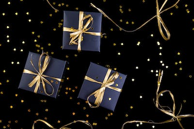 Black gift boxes with gold ribbon on shine background. Flat lay.