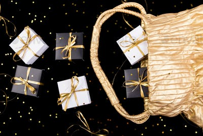 Black and white gift boxes with gold ribbon pop out from golden bag on shine background. Flat lay.