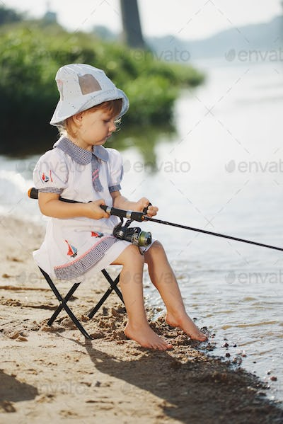happy girl with rod on coast of river