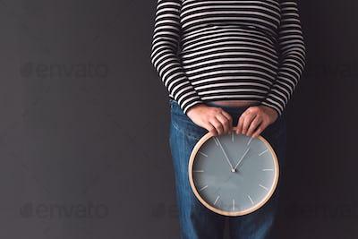 Pregnant female with vintage alarm clock