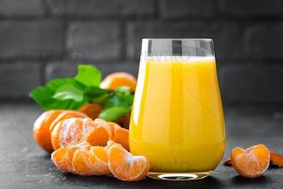 Tangerines, peeled tangerines and tangerine juice in glass