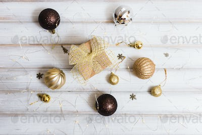 Christmas gift box with ribbon bow and ball toy on white wooden background