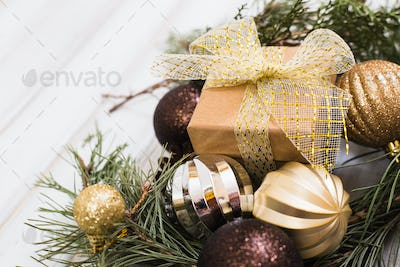 Christmas gift box with ribbon bow and branch christmas tree and ball toy and cone on white wooden