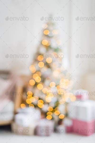 Blurred view of beautiful fir tree in decorated room for Christmas