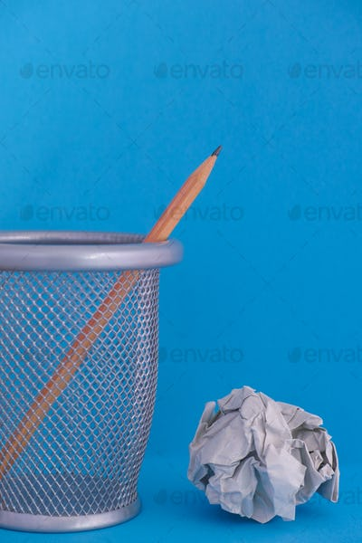 Pencil in bin with crumpled paper ball near it