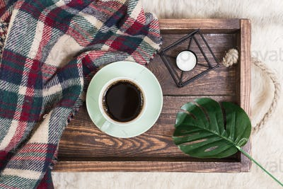 Coffee cup, tray on wooden background with a blank notepad