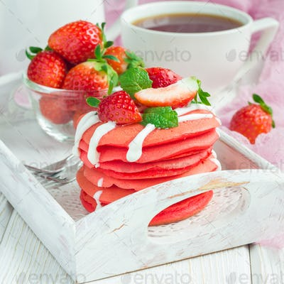 Stack of red velvet pancakes with yogurt and strawberry on on wooden tray, square