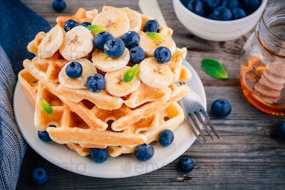 Fresh homemade waffles with blueberries and banana for breakfast