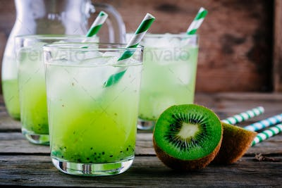 Cocktail with kiwi and mint in a glass on  wooden background.