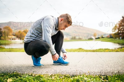 Handsome young runner tying shoelaces.