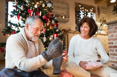 Senior couple in front of Christmas tree enjoying presents.