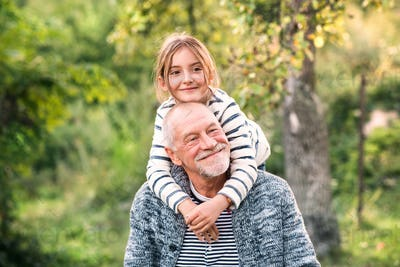 Grandfather carrying his grandaughter on his shoulders.