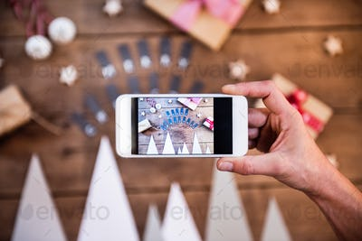 A hand holding smartphone displaying Christmas composition.