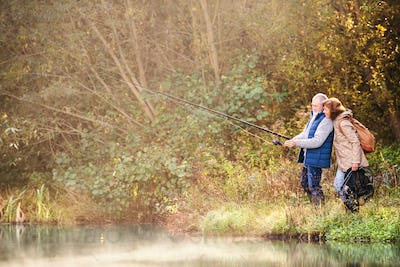 Senior couple fishing at the lake in autumn.
