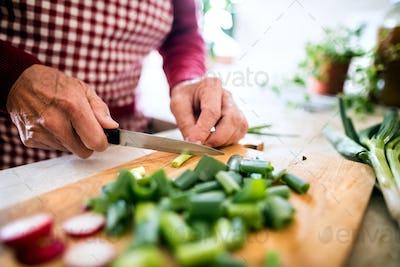 A senior man preparing food in the kitchen.
