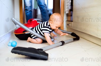 Young mother with a baby boy doing housework.