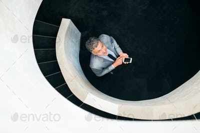 Businessman with smartphone standing at staircase.