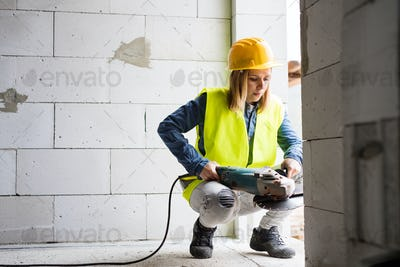 Young woman worker with electric tool on the construction site.