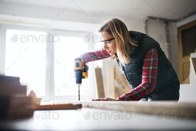 Young woman worker in the carpenter workroom.