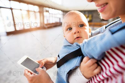 Young mother with smartphone and baby travelling.