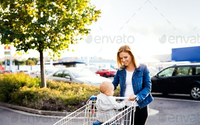 Mother with baby boy going shopping in the car park.