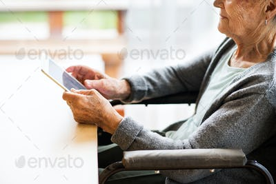 Unrecognizable senior woman in a wheelchair with tablet at home.