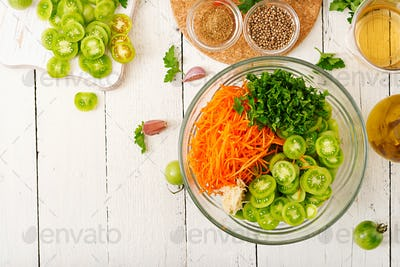 Ingredients for Korean salad from green tomatoes and carrots. Flat lay. Top view