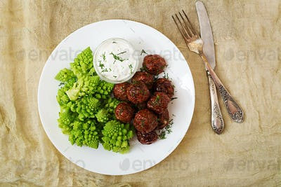 Baked beef meatballs and garnish from boiled cabbage romanesko.