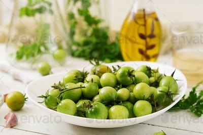 Green tomatoes in a white bowl. Preparation for pickling.
