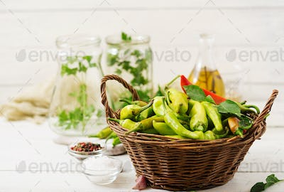Green chili peppers in a basket on a white background. Preparation for pickling.