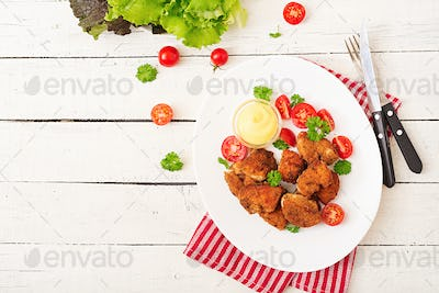 Chicken nuggets and sauce in plate on a white wooden background. Flat lay. Top view