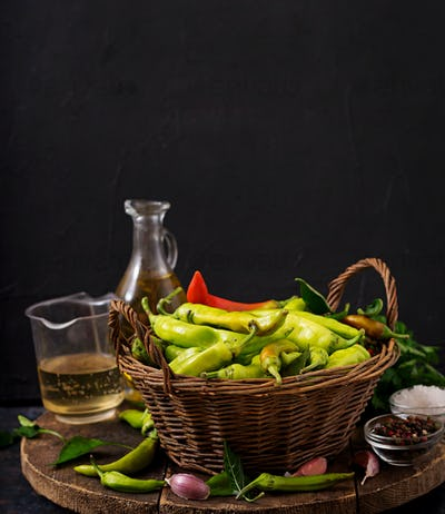 Green chili peppers in a basket on a dark background. Preparation for pickling.