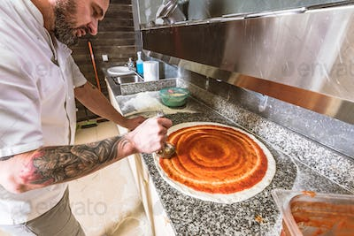 Bearded man chef preparing pizza at local business