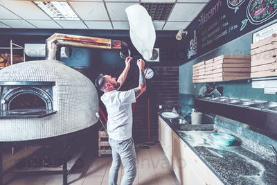 Bearded pizzaiolo chef lunching dough into air