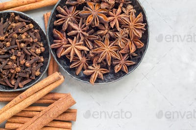 Different kinds of aromatic winter spices in bowls, top view, copy space, horizontal