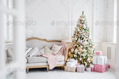 Classic Christmas light interior in white and pink tones with a couch, tree and molding in the